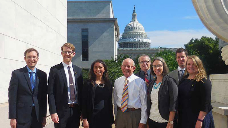 group poses for photo in business attire with capitol building in background