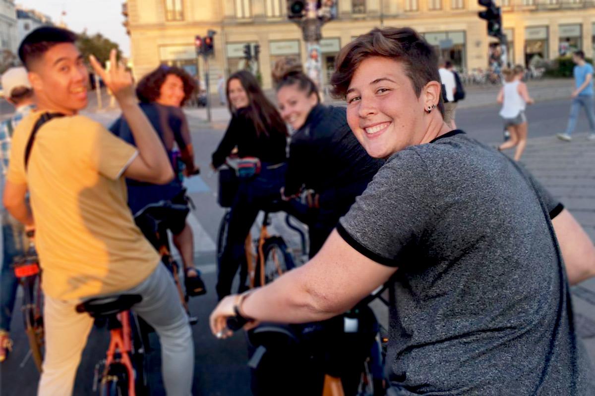 Portrait of Finley Heeb on a bike in a European city