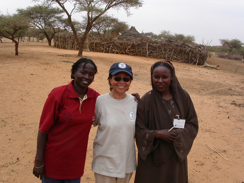 Rogers with two local villagers in Darfur, Sudan, in 2002.