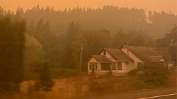 Smokey landscape in Oregon hills with a house in foreground