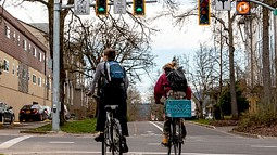 Two people on bikes at intersection