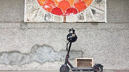 E-scooter in front of ceramic mural